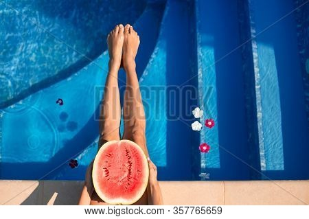 Watermelon In Pool On Woman Slim Legs In Summer Holiday Time. Tropical Beach Luxury Lifestyle. Woman
