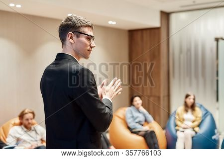Young Male Speaker In Suit Giving A Talk At Informal Business Meeting In Modern Workspace. Comfortab