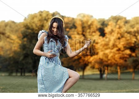 Careless Young Woman With Headphones Listening Music Dancing Like A Rock Star At The Park.