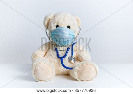 Cute Teddy Bear Doctor With Protective Medical Mask And Stethoscope. Concept Of Pediatric Treatment
