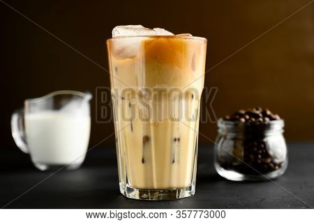 Glass Of Iced Coffee, Cream On A Black Table, Brown Background. Copy Space, Horizontal Orientation.