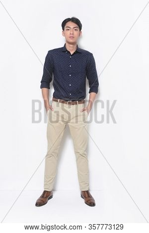 Portrait of young man, young man wearing blue shirts holds pockets standing , on white background,  full length,