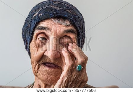 Portrait Of An Elderly Turkish Woman With Traditional Bonnet Rubbing Eye On White Background.