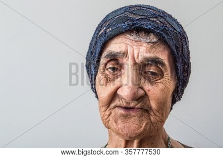 Portrait Of An Elderly Turkish Woman With Traditional Bonnet On White Background.