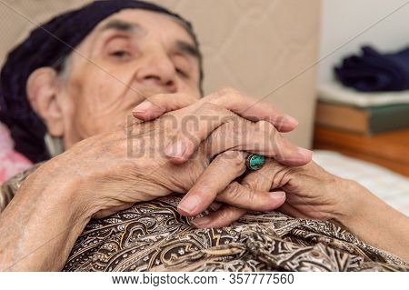 Close Up Hands Of An Elderly Woman Lying On Her Bed.
