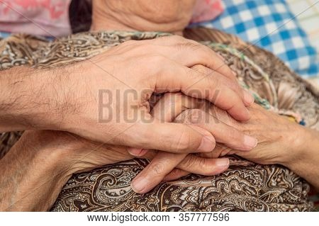 Close Up Of Male Hand Holding Elderly Female Hands, Showing Unity