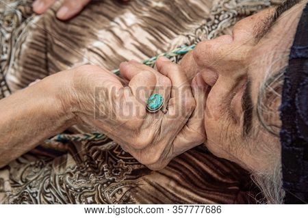 Face Of An Elderly Turkish Woman With Traditional Bonnet. Close Up Of Hand Touching Face.