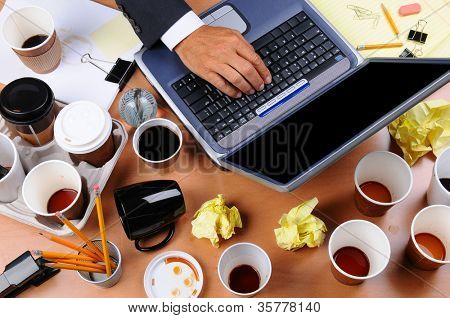Closeup view of a very cluttered businessman's desk. Overhead view with man's hand on laptop keyboard and scattered coffee cups and office supplies. Horizontal format.