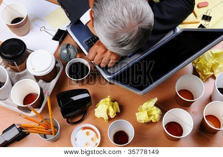 Closeup view of a very cluttered businessman's desk. Overhead view with man's head on laptop keyboard and scattered coffee cups and office supplies. Horizontal format.