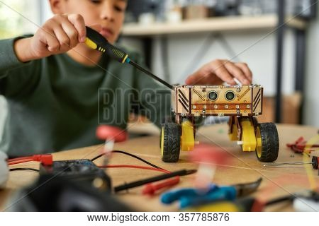 Close Up Of A Boy Using Screwdriver While Fixing Bolts On A Robot Vehicle. Smart Kids And Stem Educa