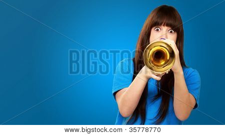 portrait of a teenager playing trumpet on blue background