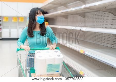 Asian Woman Looking At Supermarket Empty Toilet Paper Shelves Amid Covid-19 Coronavirus Fears, Shopp