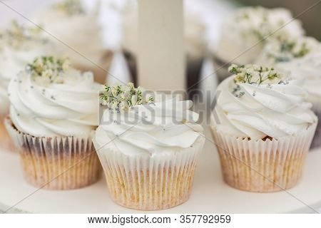 White Cream Muffins Decorated With Flowers And Silver Beads On A Tiered Stand