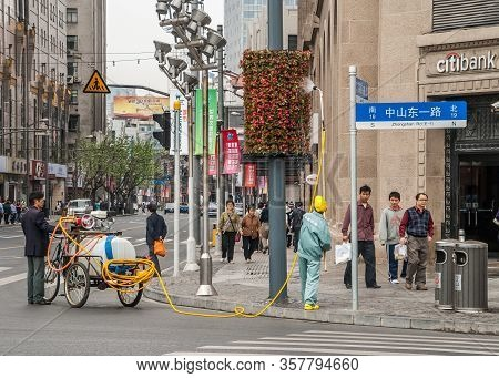 Shanghai, China - May 4, 2010: 2 Men With Tricycle Bike And Water Tank Water Hanging Flower Pieces A