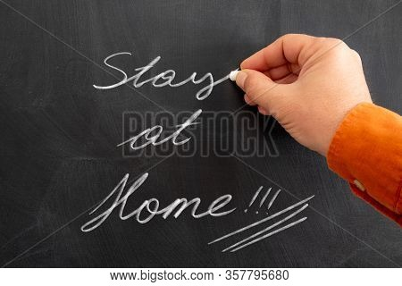 Announcement On Black Chalkboard To People, To Stay At Home To Keep Social Distance. Writing To Chal