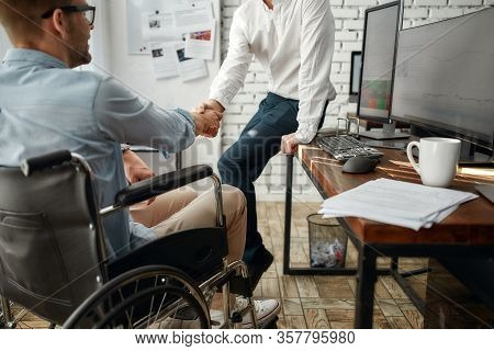 Young Male Office Worker In A Wheelchair Shaking Hand To His Colleague While Working Together In The