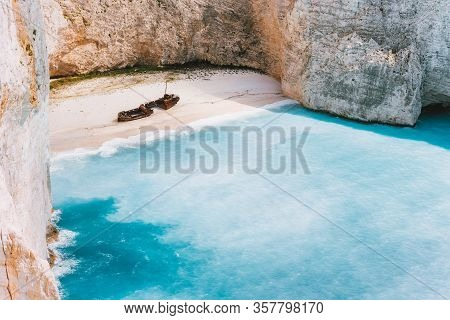 Navagio Beach With Turquoise Blue Sea Water Surrounded By Huge White Limestone Cliffs. Famous Landma
