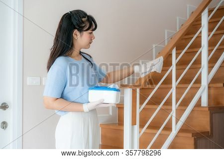 Asian Woman Disinfecting The Banister Of Staircase By Disinfectant Disposable Wipes From Box. Preven