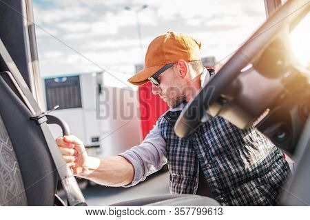 Cargo Transportation Theme. Caucasian Trucker Driver In His 30s Living His Semi Truck Cabin.