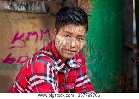 Pakokku, Myanmar - December 22, 2019: Teen With Thanaka Paste On His Face Sitting At The Myoma Marke