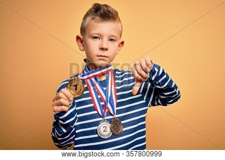 Young little caucasian winner kid wearing award competition medals over yellow background with angry face, negative sign showing dislike with thumbs down, rejection concept