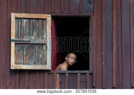 Nyaungshwe, Myanmar - December 26, 2019: A Young Monk Looking Out Window In Shwe Yanp Yay Monastery.