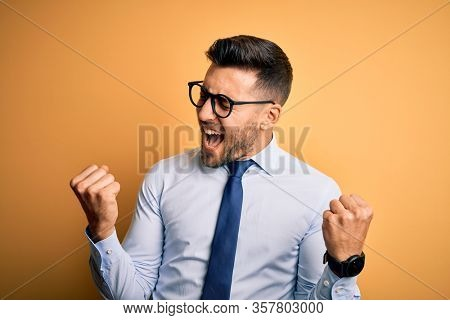 Young handsome businessman wearing tie and glasses standing over yellow background very happy and excited doing winner gesture with arms raised, smiling and screaming for success. Celebration concept.