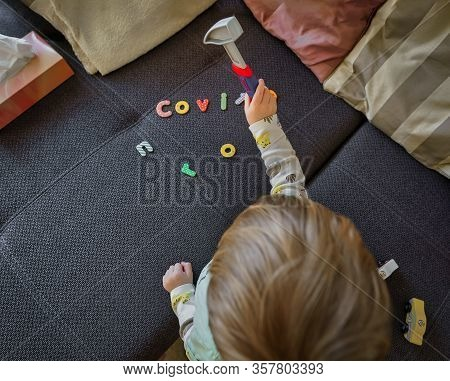 Covid-19, Corona Virus. A Little Boy Hammers The Covid Typography With A Hammer Away, A Symbol For F