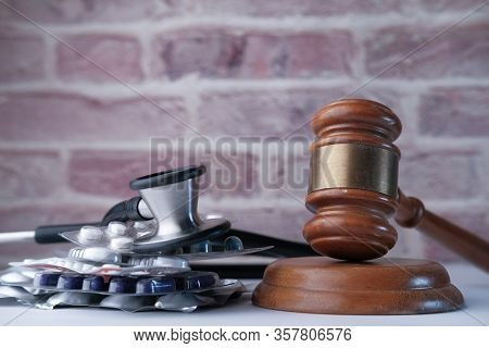 Judge Gavel And Stethoscope With Pills On Table