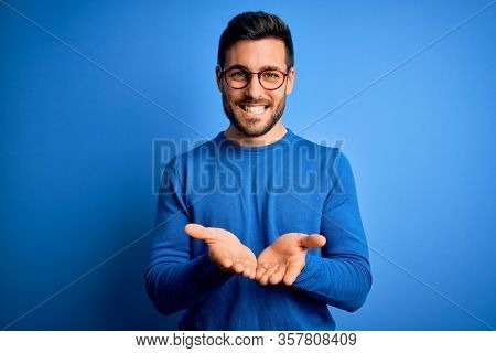 Young handsome man with beard wearing casual sweater and glasses over blue background Smiling with hands palms together receiving or giving gesture. Hold and protection