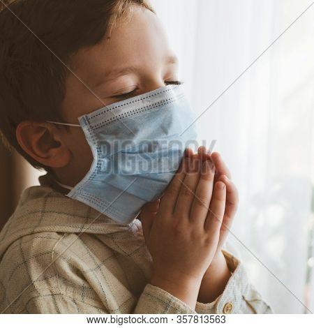 Coronavirus Covid-19. Child Praying To God Requesting That The Coronavirus Covid 19 Not Spread Beyon
