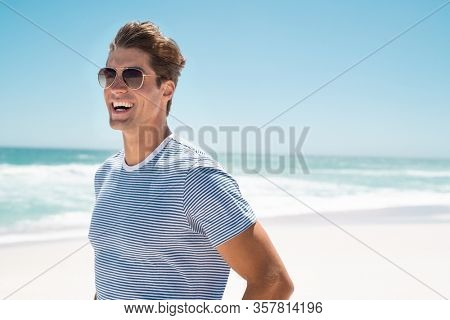 Happy young man in casual clothing wearing sunglasses and smiling at the beach. Handsome guy laughing at the beach and looking away. Portrait of cheerful guy enjoying summer vacation with copy space.