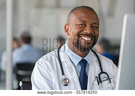 Happy smiling african doctor looking at camera in office. Portrait of black man doctor working on laptop. Confident and reliable mature nurse using computer to analyze medical report of patient.
