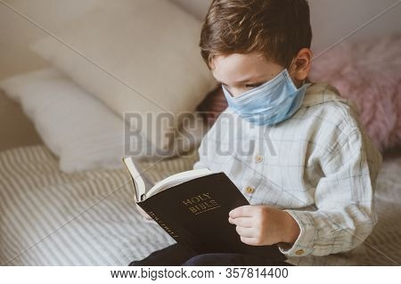 Coronavirus Covid-19. The Child Holds A Bible. Bible Readings And Prayer. Peace, Hope Concept.