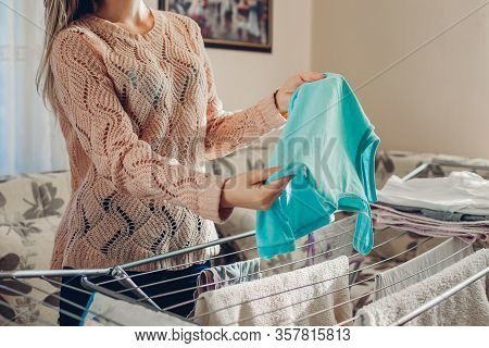 Young Woman Housewife Hanging Clean Clothes On Dryer After Washing At Home. Housekeeping And Househo