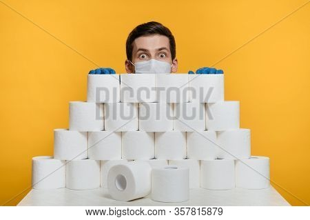 Scared Man In A Protective Face Mask Is Hiding Behind Toilet Paper To Protect Himself From Coronavir