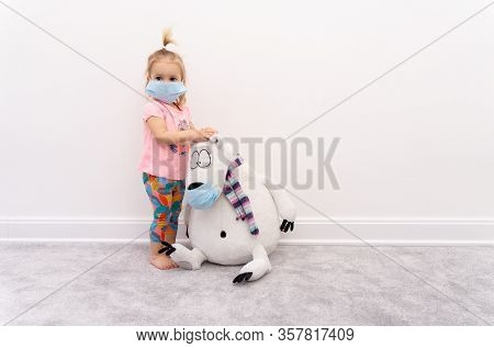 Little Blond Caucasian Girl Baby In Protective Mask Sits Isolated At Home At Quarantine With White B