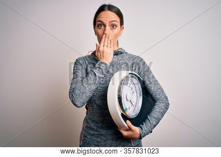 Young fitness woman wearing sport workout clothes holding scale for healthy weight cover mouth with hand shocked with shame for mistake, expression of fear, scared in silence, secret concept