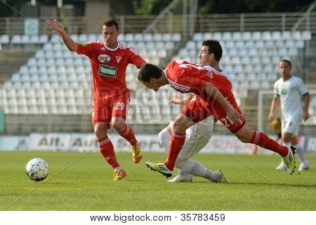 KAPOSVAR, HUNGARY - AUGUST 4: Unidentified players in action at a Hungarian National Championship soccer game Kaposvar (white) vs Debrecen (red) August 4, 2012 in Kaposvar, Hungary.