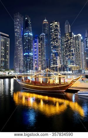 Dubai, Uae - November 15: The Night Illumination Of Dubai Marina And Traditional Dhow Boat,  On Nove