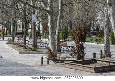 Empty Spring City Alley. Empty Benches And A Play Area For Children. Spring Sunny Day In A European