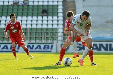 KAPOSVAR, HUNGARY - AUGUST 4: Lorant Olah (white 14) in action at a Hungarian National Championship soccer game Kaposvar (white) vs Debrecen (red) August 4, 2012 in Kaposvar, Hungary.