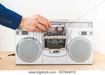 Image Of Man Playing An Old Radio Indoors. Close Up Of Vintage Radio. Man Using Cassette On Old Radi