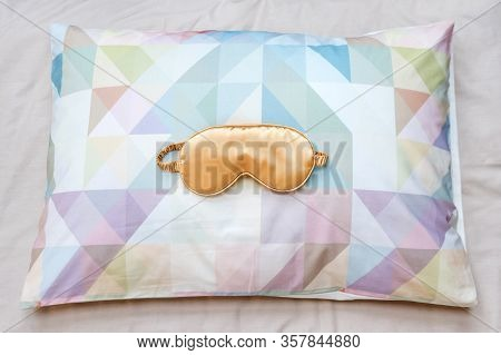 Golden Sleeping Eye Mask On The Bed, Top View. Good Night, Flight And Travel Concept. Sweet Dreams,