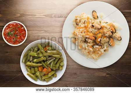 Rice With Mussels And Carrots On A White Plate. Rice With Mussels And Carrots On A Borwn Wooden Back