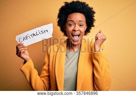 African American afro businesswoman with curly hair holding paper with capitalism message screaming proud and celebrating victory and success very excited, cheering emotion