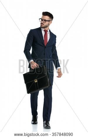 attractive businessman wearing glasses walking with briefcase on hand and looking away tough on white studio background