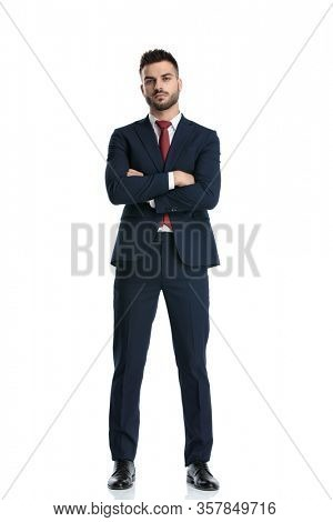 sexy formal man wearing navy suit standing with hands crossed and striking a pose with tough attitude on white studio background