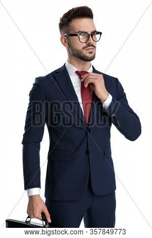 attractive businessman wearing glasses standing and holding a briefcase while fixing his tie with tough attitude on white studio background