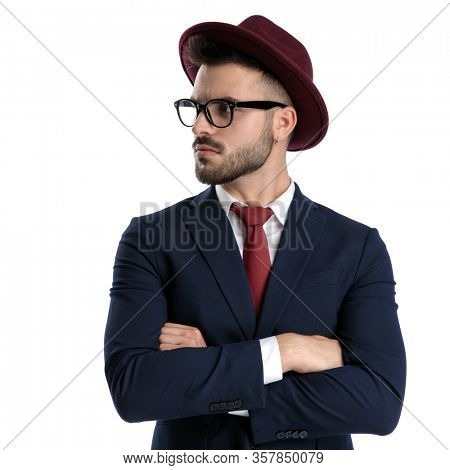 attractive businessman wearing burgundy hat standing with arms crossed to chest and looking aside tough on white studio background